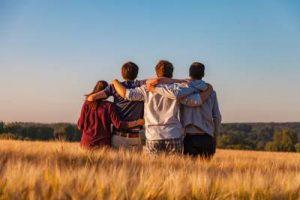 Familia de cara al océano fundidos en un abrazo grupal. Terapia familiar.